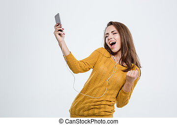 Woman listening music in headphones and dancing