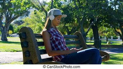 Woman listening music in park 4k - Beautiful woman listening...
