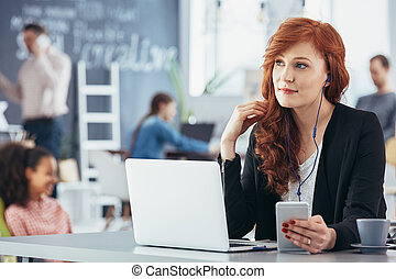Woman listening music while working - Attractive woman...