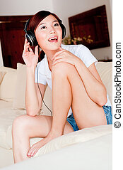 Woman Listening To Music - A pretty young Asian woman...