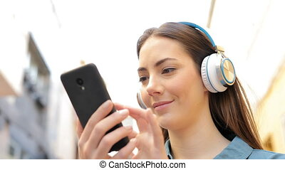 Woman listening to music checking songs - Serious woman...
