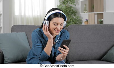 Woman listening to music from cell phone - Happy woman...