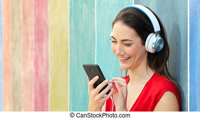 Woman listening to music in a colorful wall - Happy woman...