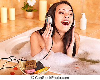 Woman listening to music in bath - Woman listening to music...