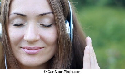 Woman listening to music in headphones on the outdoor. Portrait of a beautiful close-up girl.