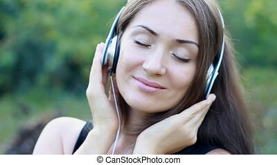 Woman listening to music in headphones on the outdoor. Portrait of a beautiful close-up girl