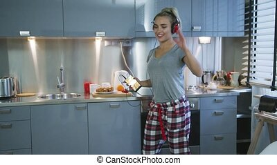 Woman listening to music in kitchen - Pretty young woman in...