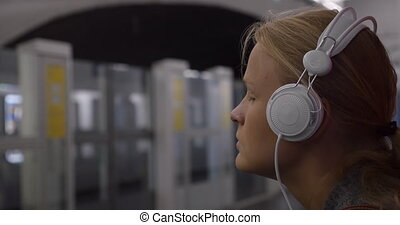 Woman listening to music in subway