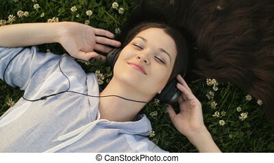 Woman listening to music lying on the grass