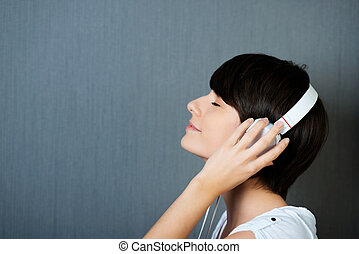 Woman listening to music on earphones with her hands to her...