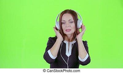 Woman listening to music on headphones. Green screen - Woman...