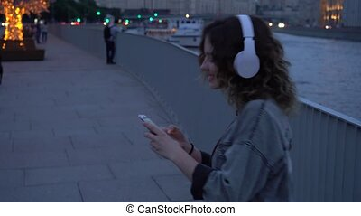 Woman listening to music on her smartphone in city - girl in...
