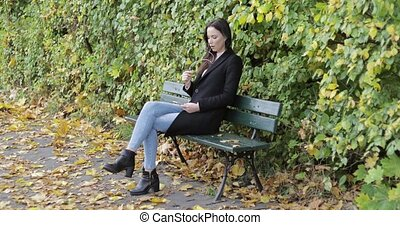 Woman listening to music on park bench