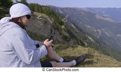 Woman listening to music on the mountain top