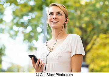 Woman Listening To Music Through Headphones Using Mobile Phone