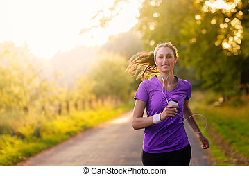 Woman listening to music on her earplugs and MP3 player while jogging along a country road in a healthy lifestyle, exercise and fitness concept
