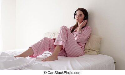 Woman listening to music with big headphones on the bed in