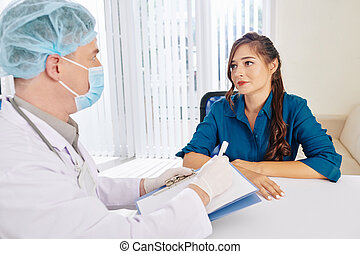 Woman listening to recommendations of doctor - Pretty ...