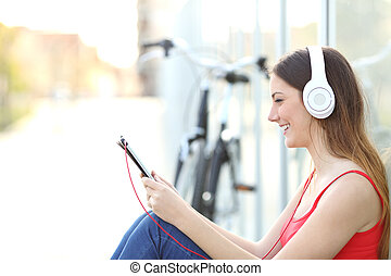 Woman listening to the music from a tablet sitting on the floor in a park with a bicycle in the background