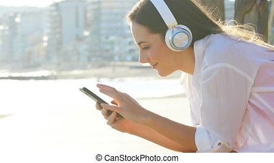 Woman listening to the music in the coast - Profile of a...