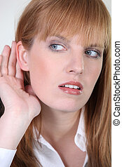 Woman listening with her hand behind the ear