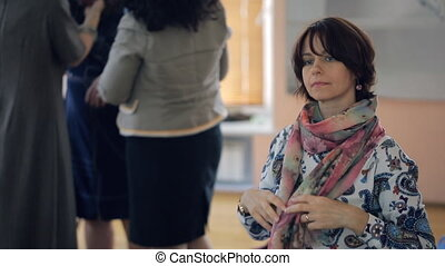 Woman listens carefully and ties beautiful scarf on neck at the same time.