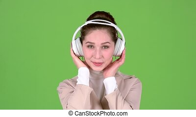 Woman listens to melodious songs in the headphones. Green...