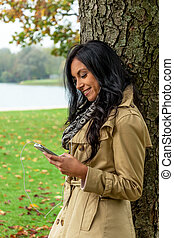 woman listens to music on mobile phone - a young woman ...