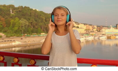 woman listens to the music - lady wearing blue headphones....