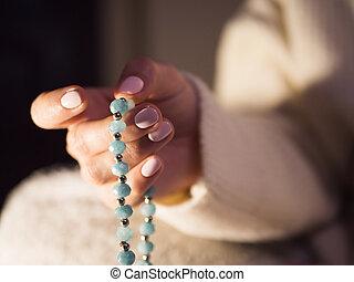 Woman, lit hand close up, counts Malas, strands of gemstones...