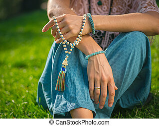 Woman, lit hand close up, counts Malas, strands of wooden...