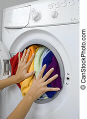 woman loading laundry in the washing machine