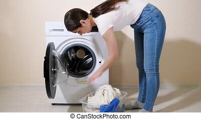 woman loads dirty clothes into washer near beige wall - ...