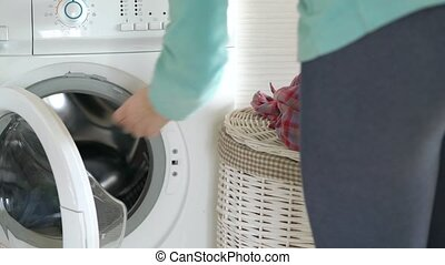 Woman loads the laundry in the washing machine