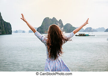 Woman look on HALONG bay in Vietnam and rise hands. UNESCO World Heritage Site.