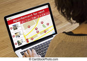 woman lookin apartment for rent on her laptop - apartment...