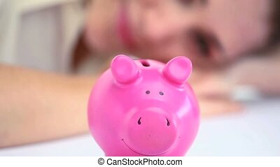 Woman looking a piggy bank while resting on a table
