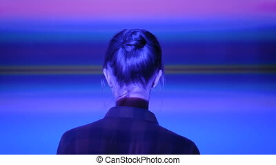 Woman looking around at modern exhibition with multi color light illumination