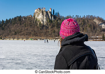 Woman looking at a castle situated on rock.