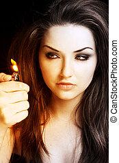 Woman looking at a lighter - A young woman firing a lighter...