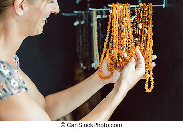 Woman looking at a necklace made of amber