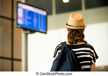 Woman looking at airport flight information board