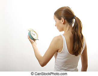 woman looking at alarm clock