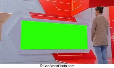 Woman looking at blank large interactive wall display - green screen concept