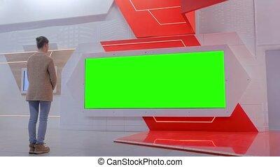 Woman looking at blank large interactive wall display -...