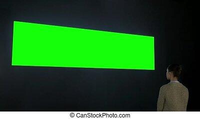 Woman looking at blank wide interactive wall display - green...