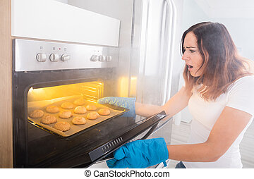 Woman Looking At Burnt Cookies Near Oven
