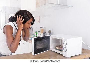 Woman Looking At Burnt Pizza In Microwave Oven - Shocked...