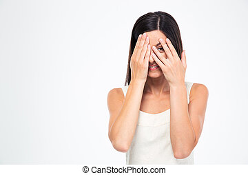 Woman looking at camera through fingers