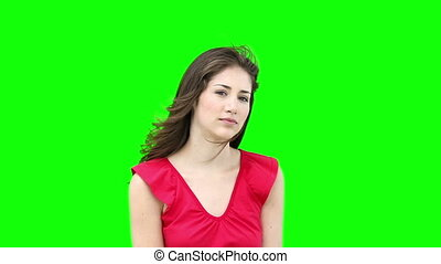 Woman looking at camera while fixing her hair